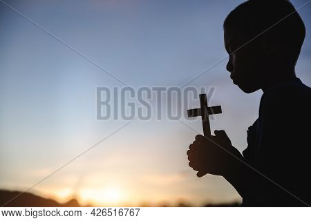 Silhouette Of Child  Praying With Cross  In Nature Sunrise Background,  Crucifix, Symbol Of Faith. C