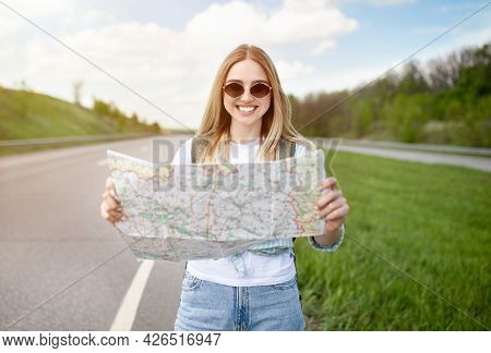 Blonde Young Lady Standing With Map On Highway, Catching Ride, Hitchhiking On Roadside, Having Autos