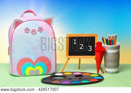 Back To School. Colorful School Equipment, A Bright School Backpack And A Blackboard With Numbers 1