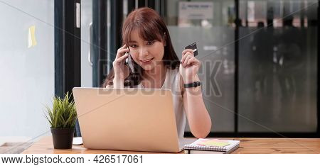 Smiling Woman Sitting Office Talking On Mobile Phone Making Online Payment On Her Tablet Computer.