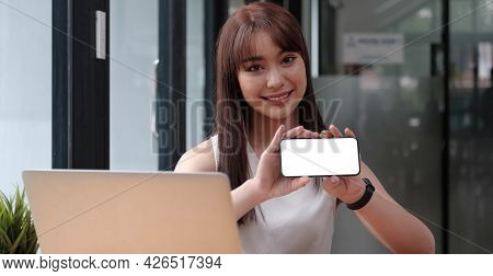 Smiling Happy Woman In Casual Showing Blank Smartphone Screen While Looking At The Camera Isolated O