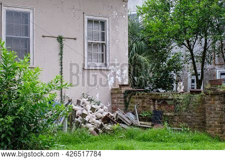 New Orleans, La - July 6: Rubble Pile In Backyard Of House Guarded By Cat On A Brick Wall On July 6,