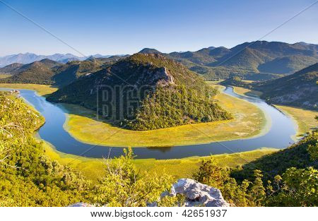 Sinuous river flowing through mountains. Rijeka Crnojevica. Located near Skadar Lake, Montenegro, Europe. Beauty world.