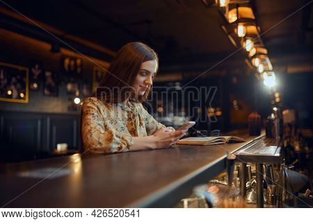 Woman with mobile phone sitting at counter in bar