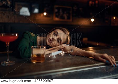 Drunk young woman sleeping at the counter in bar