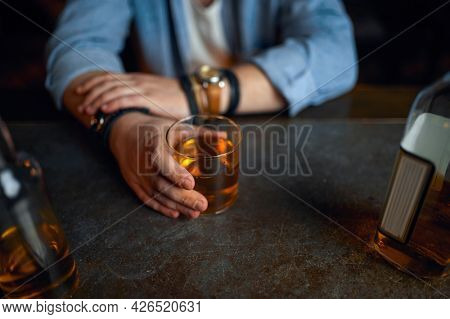Drunk man pours alcohol at the counter in bar