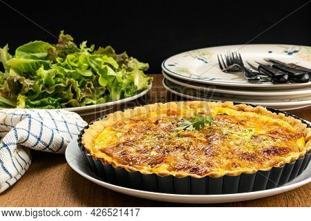 Side View Of Homemade Bacon Spinach Quiche In Black Metal Oven Pie Baking Plate On White Ceramic Dis
