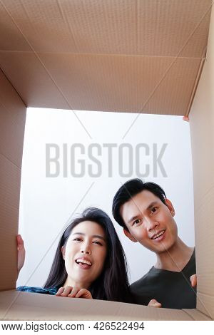 Asian Couple Moving Into A New Home Open A Large Brown Cardboard Box. Happy Smile. Family Concept Th
