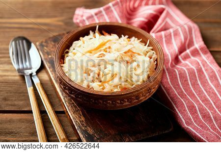Sauerkraut, Fermented Cabbage With Carrots In Bowl On Wooden Background With Copy Space.