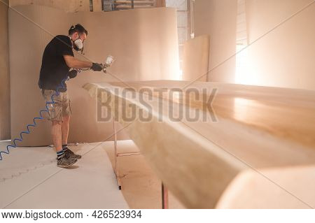 Man In Respirator Mask Painting Wooden Planks At Workshop