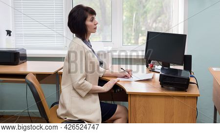 A Primary School Teacher Conducts Lesson Sitting At A Table.
