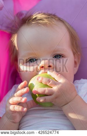 A Little Girl Sitting In A Baby Carriage With A Big Appetite Eats An Apple.