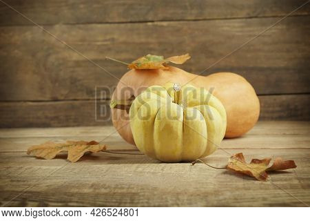 Autumn Still Life Of Pumpkin And Maple Leaves. Autumn Seasonal Background On A Wooden Background. He