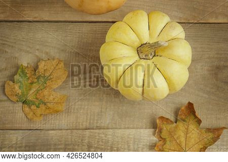 Autumn Still Life Of Pumpkin And Maple Leaves. Autumn Seasonal Background On Wooden Background. Than