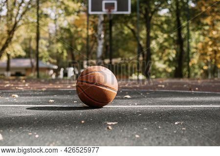 Basketball Ball On The Sports Field. Healthy Lifestyle And Sport Concepts. Court With Hoop On The Ba