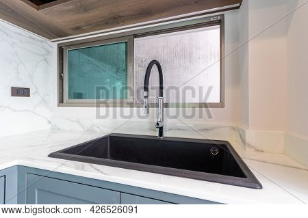 Luxurious Modern Black Sink On A Marble Kitchen Countertop At House