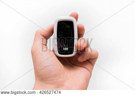 Man's Hand Holds Medical Modern Pulse Device Oximeter Close-up On White Background.