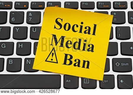 Social Media Ban Message On Yellow Sticky Note On A Black And Silver Keyboard