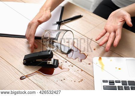 Woman Spilled Coffee On Wooden Office Desk, Closeup
