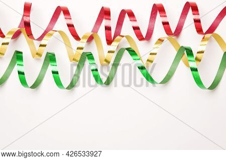Horizontal Photo Of Green, Yellow And Red Paper Streamers On White Background With Copy Space.