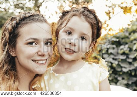 Cute Little Redhead Girl And Happy Young Mother With Similar Braided Hairdo Hugging Together