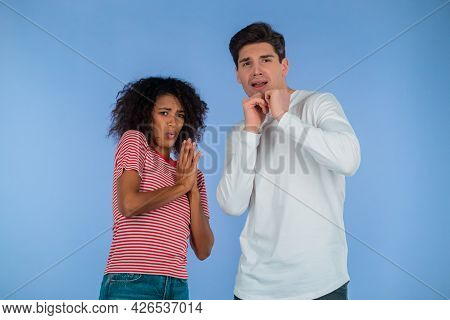 Frightened Interracial Couple Afraid Of Something And Looks Into Camera With Big Eyes Full Of Horror