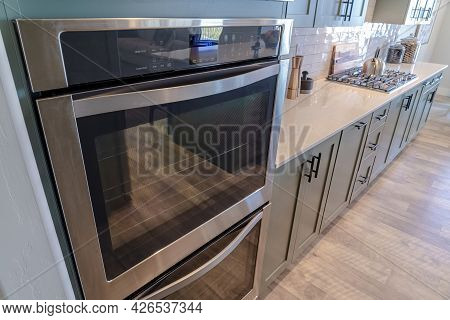 Oven And Countertop With Stove Inside The Kitchen Of Home With Wooden Floor