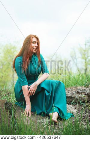 Beautiful Woman In Elegant Dress Sits On Rocks In Forest. Girl In Woodland On Background Of Green Tr
