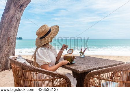 Woman In White Dress And Straw Hat Sitting On Table In Outdoor Beach Cafe With Blue Sea. Female Drin