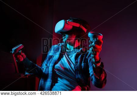 Caucasian Woman 35-40 Years Wearing Virtual Reality Headset And Gesturing While Sitting In Neon Ligh