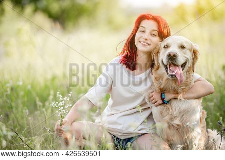 Teen girl with red hair hugging golden retriever dog at the nature and smiling. Pretty young female with doggy pet in the sunny field