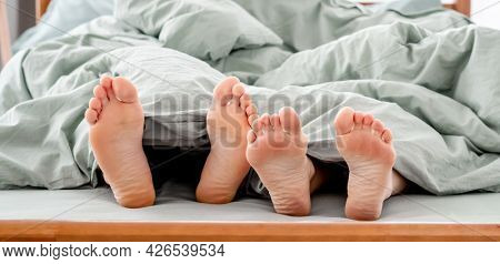 Feet of couple in the bed under the blanket. Legs og man and woman together in the bedroom in the morning. Concept of rest, love and happy family relationships