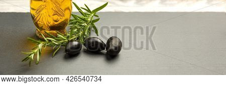 Olive Oil. Olives On A Background Of Olive Oil. A Bottle Pours Oil Into A Saucer Close-up. Black Sto