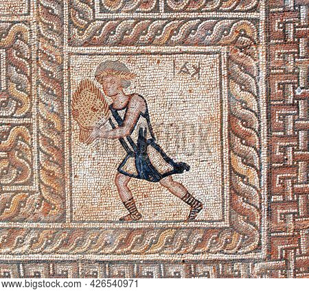 Detail of ancient mosaic with boy with shell. Decorative stone mosaic on floor in baths, Dion, Pieria, Greece
