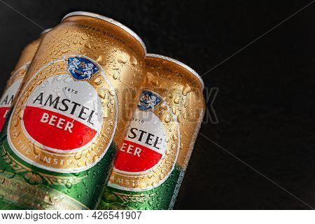 Beer Cans With Water Drops. Amstel Beer In Wet Cans On Wet Black Background With Copy Space. An Inte