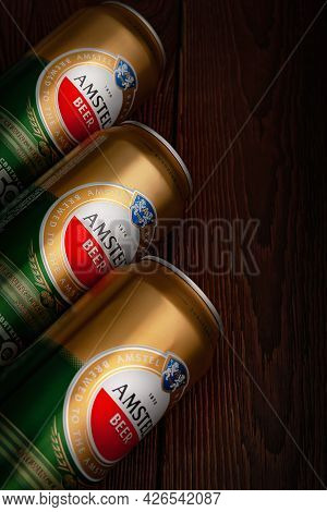 Beer Cans. Amstel Beer In Cans Close-up On A Dark Brown Background With Copy Space. An International