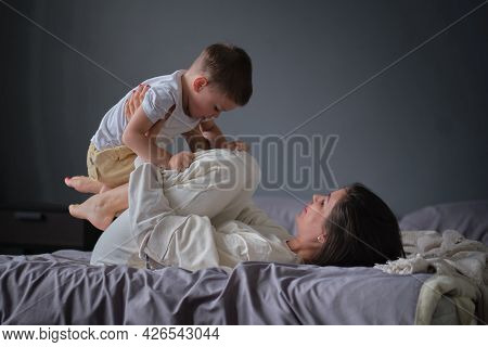 Mom Lying In Bed Have Fun Play With Cute Little Son. Joyful Young Strong Woman Lifting On Legs Arms