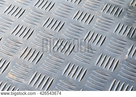 Detail Of A Silver Stainless Steel Floor. There Is A Corrugation That Resembles A Braided Pattern. B