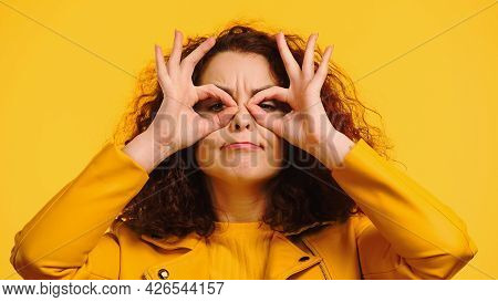 Young Curly Woman Imitating Eyeglasses With Hands And Grimacing Isolated On Yellow