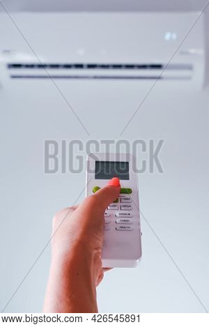 Air Conditioning. A Woman Holds A Remote Control From An Air Conditioner In Her Hands. Wall Mounted
