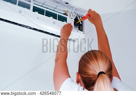 Repair Of The Air Conditioner. A Woman With A Screwdriver In Her Hands Is Repairing An Air Condition