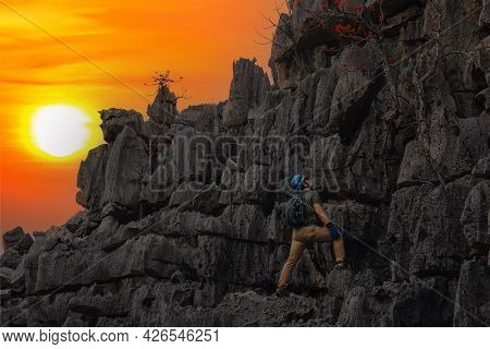 Man Looking Up At The Mountain He Is About To Climb. Man Climbing A High And Dangerous Mountain. Man