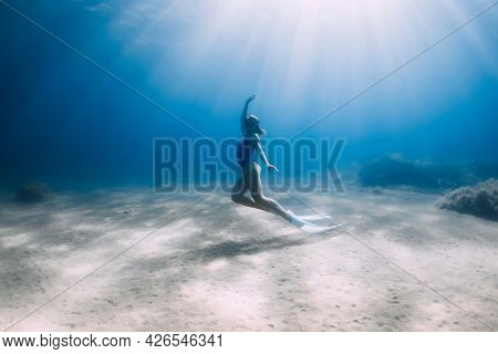 Lady Free Diver In Swimsuit Posing Underwater At The Deep In Blue Ocean With Sunlight.