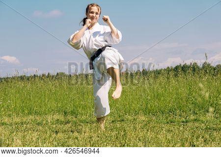 Teenage Girl Practicing Karate Kata Outdoors, Prepares To Yoko Geri Kick