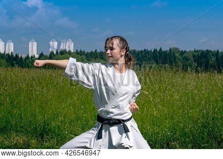 Teen Girl Performing Karate Kata Outdoors In Kiba-dachi Stance