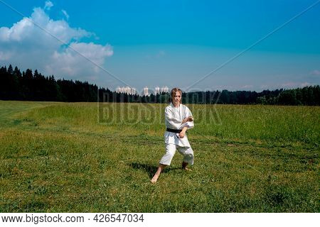 Teenage Girl Practicing Karate Kata Outdoors, Prepares To Perform Downward Block Gedan Barai In Zenk