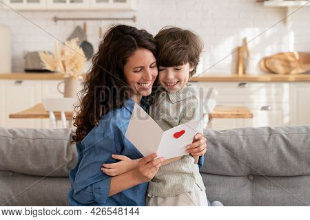 Adorable Little Kid Son Embrace Smiling Mother Holding Paper Postcard With Holiday Wishes Read Greet