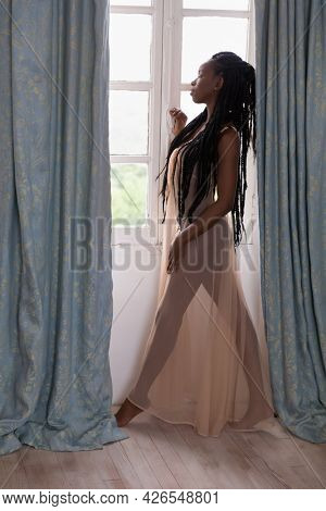 Beautiful woman in sheer nightgown looking out of a window with backlighting