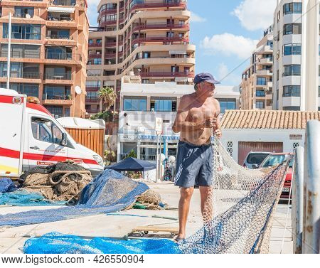 Calpe Spain- August 24 2016; Fisherman Standing Bare-chested  Drying And Mending His Blue Fishing Ne