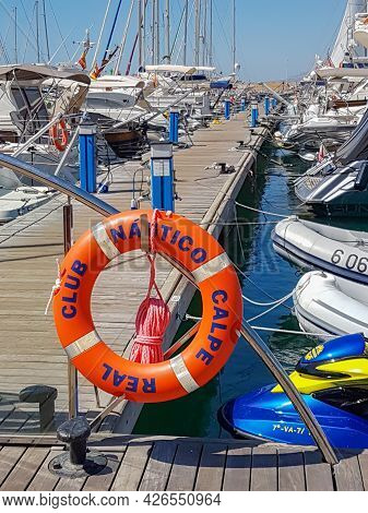 Calpe Spain - August 24 2016; Long Marina Pier With Boats Moored Along Both Sides And Orange Buoy Wi